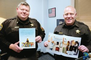 """Winchester Sheriff's Office Maj. Al Sibert (left), and Sheriff Les Taylor, hold copies of """"Deputy Knowles Knows,"""" a book produced by the Sheriff's Office. (Photo by Scott Mason/The Winchester Star)"""